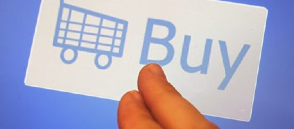Mans fingers touching a white Shopping cart and Buy sign on a blue background conceptual of making a purchase during online shopping and e-commerce