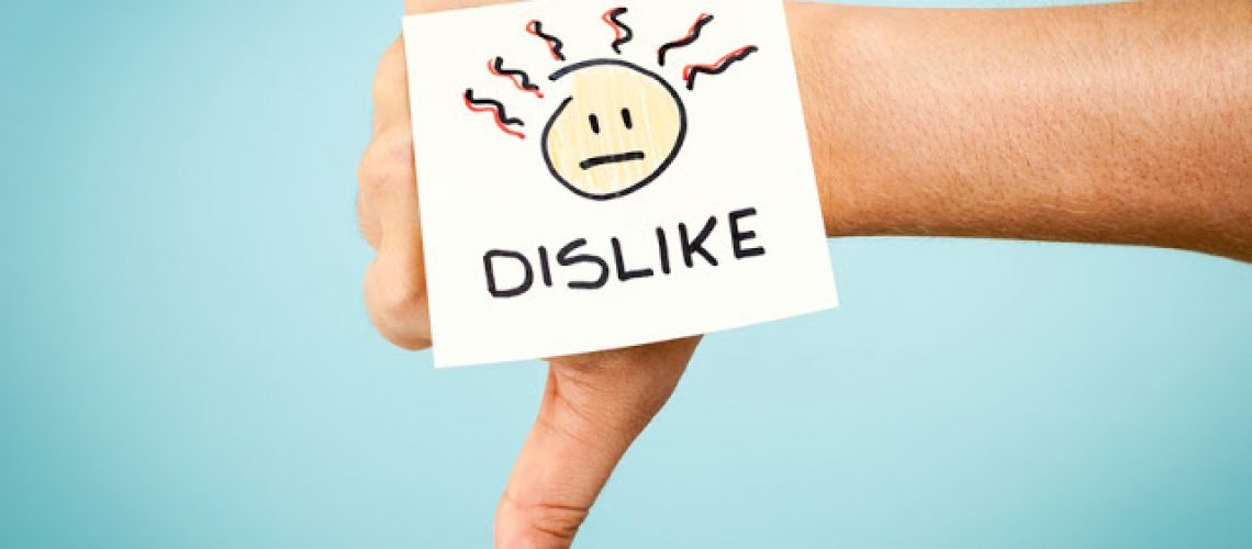 Dislike concept with hand on blue background